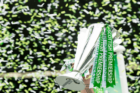 Celtic green and white confetti floating behind a silver trophy cup