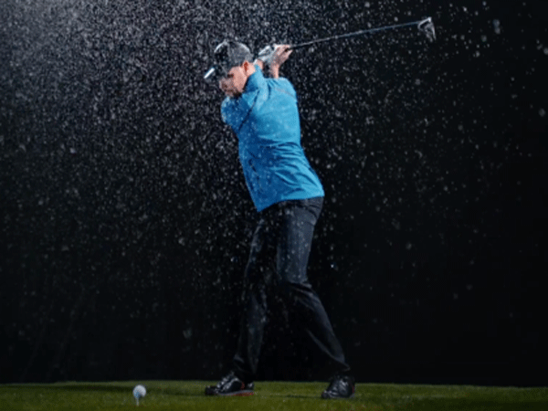 Golfer about to hit the ball in a rain curtain