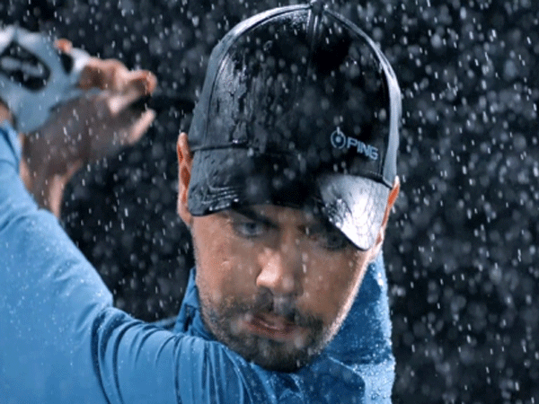 Golfer standing with a rain curtain background