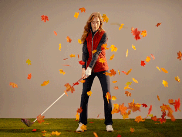 Women golfer playing surrounded by leaves